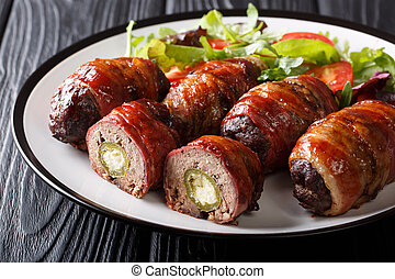 American Texas Armadillo eggs with jalapeno and cheese wrapped in bacon served with fresh salad close-up on the table. horizontal