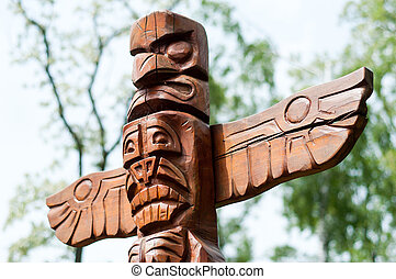Wooden Native American single totem standing in the forest.
