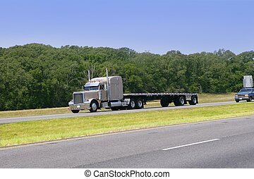 American Truck driving on a road with green forest