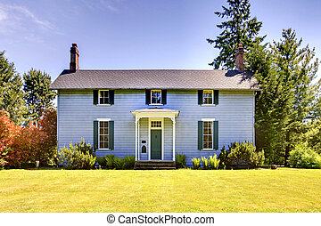American two story house with blue exterior paint and small open porch.