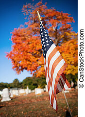 American veteran flag in autumn cemetery