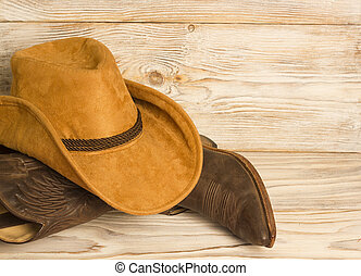 American West cowboy boots and hat on wood texture background for text
