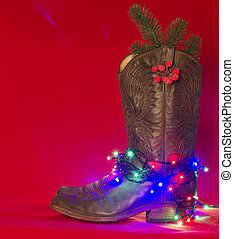 American West traditional boots on christmas red background for text