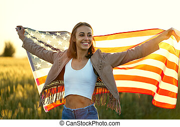American woman proudly holding American flag at sunset field, celebrate 4th of July
