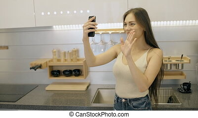 American woman talks in front of gadget with smile in lighting room.