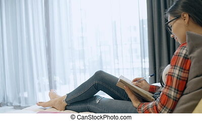 American woman writes in notebook with smile sitting on sofa...
