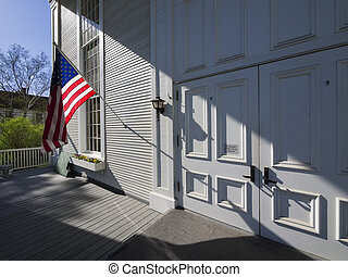 American flag back lit on front of New England church
