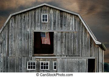 American flag hanging in a hayloft window.