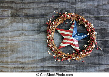 Americana metal star and wreath hanging on old, weathered wood wall.