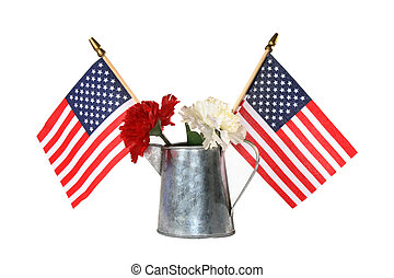 Two American flags, red and white flowers in metal can, isolated over white