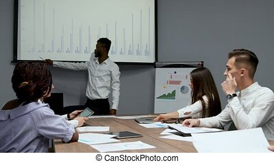 americano africano, allenatore, dà, presentazione sociale, per, businesspeople, in, ufficio, scuro sbucciato, uomo affari, presenta, affari nuovi, piano, su, whiteboard, parlante, a, clienti, ascolto, altoparlante, a, riunione