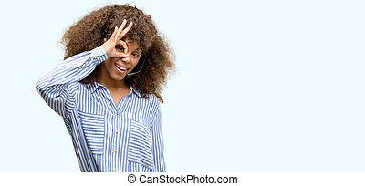 americano africano, centro chiamata, operatore, donna, con, faccia felice, sorridente, fare, segno giusto, con, mano, occhio, guardando attraverso, dita