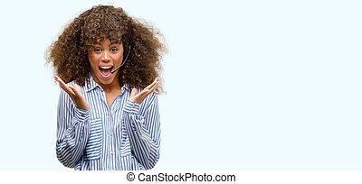 americano africano, centro chiamata, operatore, donna, molto, felice, e, eccitato, vincitore, espressione, festeggiare, vittoria, grida, con, sorriso grande, e, mani elevate