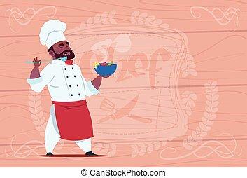 americano africano, chef, cocinero, placa de valor en cartera, con, sopa caliente, sonriente, caricatura, jefe, en, blanco, restaurante, uniforme, encima, de madera, textured, plano de fondo