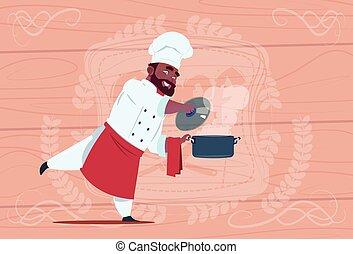 americano africano, chef, cocinero, tenencia, cazo, con, sopa caliente, sonriente, caricatura, jefe, en, blanco, restaurante, uniforme, encima, de madera, textured, plano de fondo
