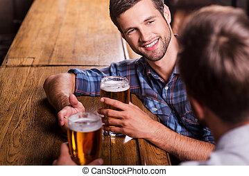 amichevole, discorso, in, bar., vista superiore, di, due, felice, giovani uomini, parlando, altro, e, gesturing, mentre, bere, birra, a, il, sbarra contraddice