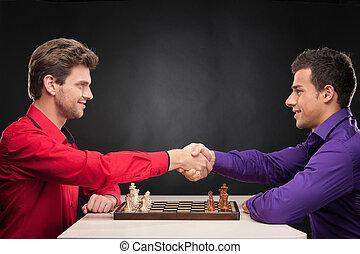 amici, gioco scacchi esegue, su, nero, fondo., sorridente, giovani uomini, stringere mano