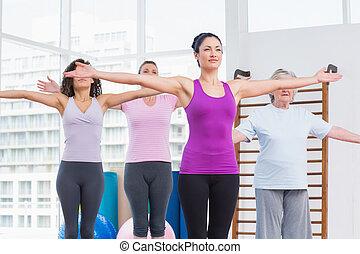 amigos, com, braços estendido, exercitar, em, ginásio