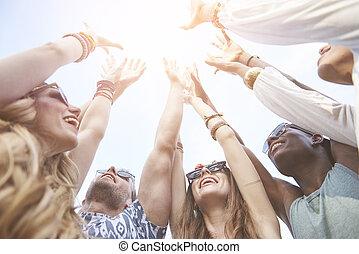 amigos, con, manos levantar, alto, en el aire