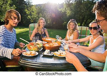 amigos, desfrutando, refeição, em, ajardine parte