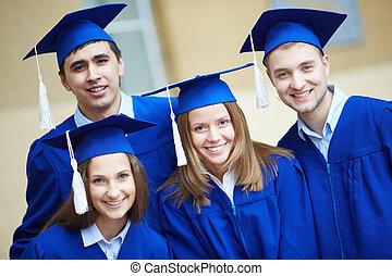 amigos, en, trajes de ceremonia de entrega de diplomas