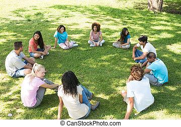 amigos, parque, sentado, círculo