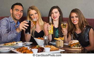 amigos, tendo jantar, junto, sorrindo, câmera