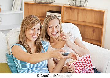 amis, femme, salle séjour, televison, regarder, sofa, pop-corn, deux, clair, manger