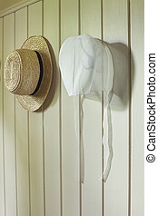 Amish bonnet and straw hat hanging on wall - An Amish...