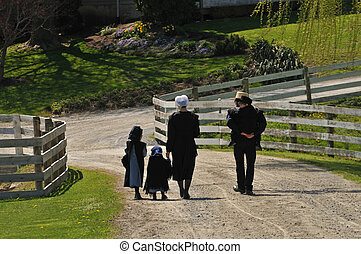 Amish family walking on the road in Pennsylvania Dutch country
