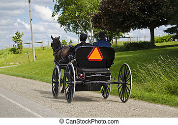 Amish (mennonite) people riding their buggy on modern road
