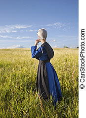 Amish woman standing in grassy field with afternoon sunlight...