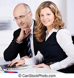 amistoso, mujer de negocios, trabajando, con, un, colega