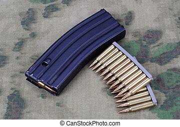 Ammunition with magazine on camoflage background