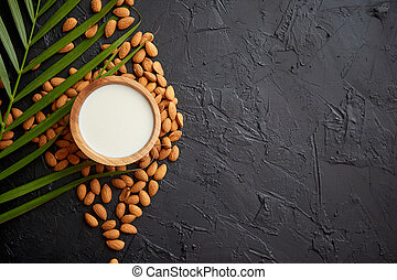 Amond seeds with bowl of fresh natural milk placed on black stone background