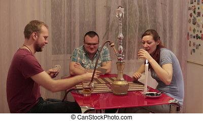Among friends smoking shisha and playing cards