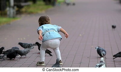 Among pigeons - Little girl being among pigeons trying to...