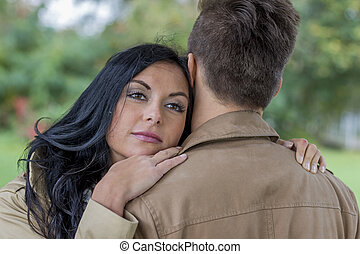 amorous couple in a park - a young, lost couple in a park