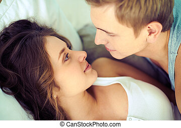 Amorous couple - Young affectionate couple looking at one...