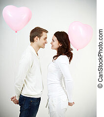 Amorousness - Two beautiful young people with heart-shaped...