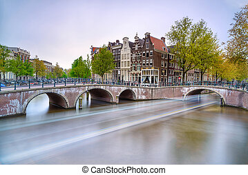 Amsterdam. Bridge and water canal. Boat light trail on...