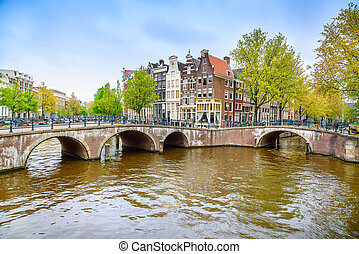 Amsterdam. Bridge and water canal on sunset. Holland or...