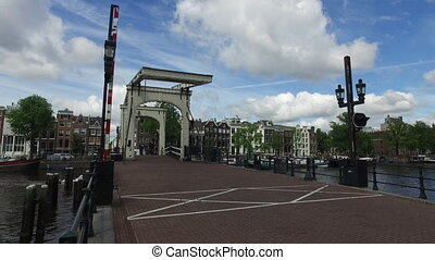Amsterdam bridge - The Magere Brug. People with a bycicle is...