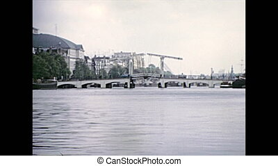 Sea view of Amsterdam bridges in 70s by boat tour in Amsterdam town of Holland. Historical archival touristic cruise in the capital city of Netherlands in the 1970s.