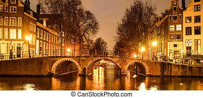 Amsterdam by night. Illuminated bridge over water canal, gracht. Netherlands.