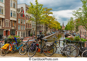 City view of Amsterdam canal and bridge with bikes, typical houses, church and boats, Holland, Netherlands.