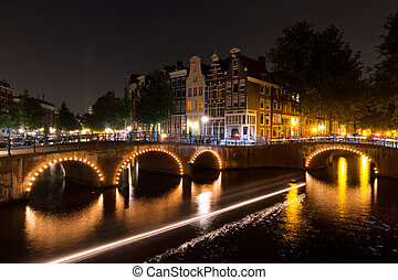 Amsterdam canal at night - Tourboat creating stripes of...