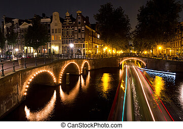 Amsterdam canal lights - Stripes of light of a tourboat...