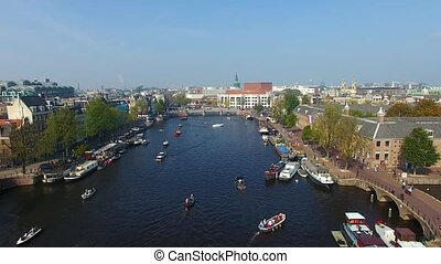 Tourist boats in the canal of Amsterdam, aerial view