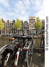 Canal  scene with a bicycles, boats and traditional Dutch houses in Red Light District. Amsterdam. Netherlands